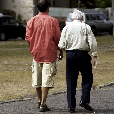 A younger and older man are walking together on a level, safe garden path.